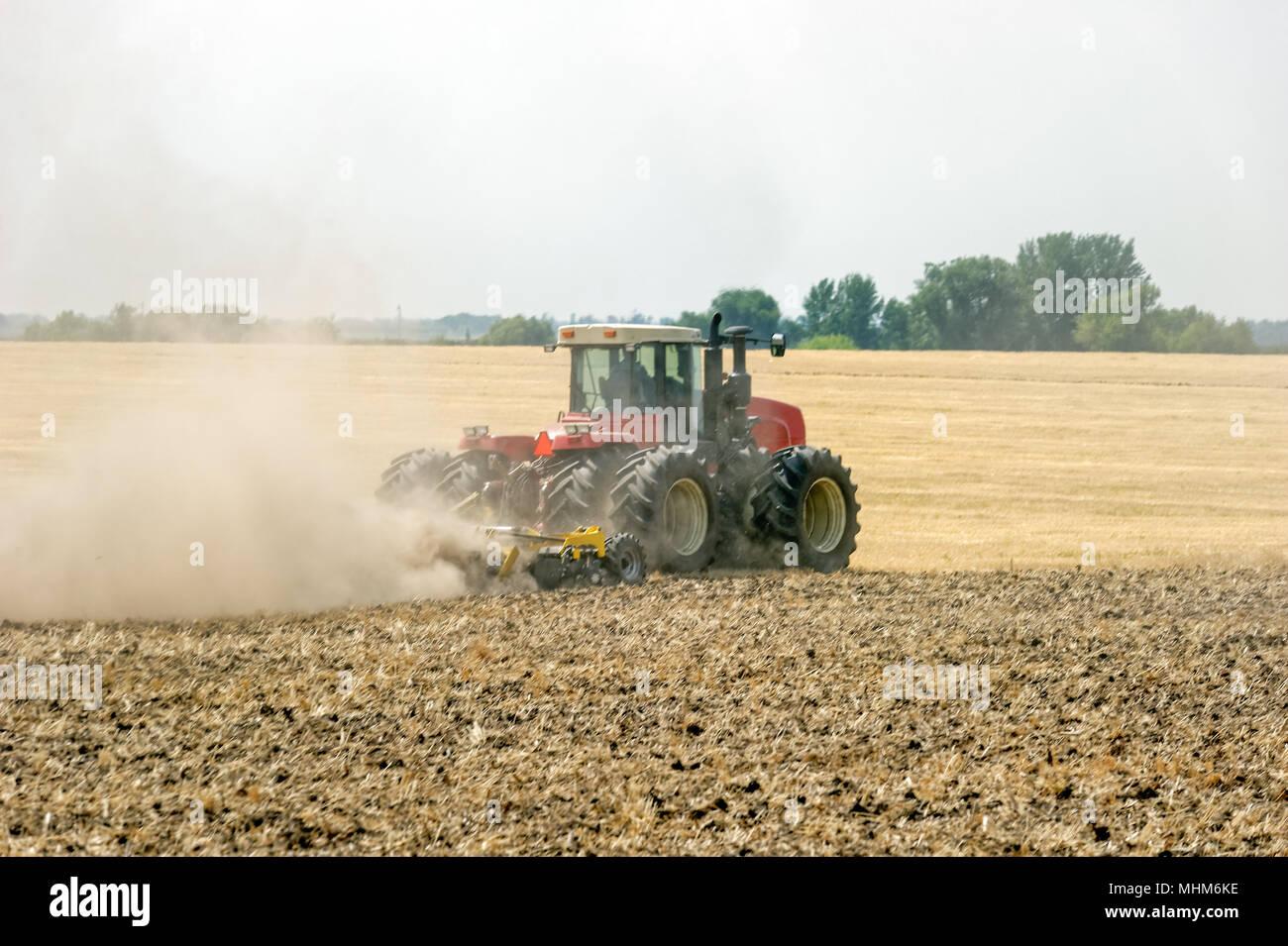 Preparación de la tierra del tractor con el arado, un día soleado de verano en el ámbito agrícola Foto de stock