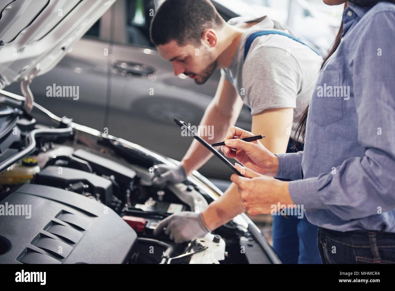 Un hombre y una mujer mecánico cliente mire el coche campana y discutir las reparaciones Imagen De Stock