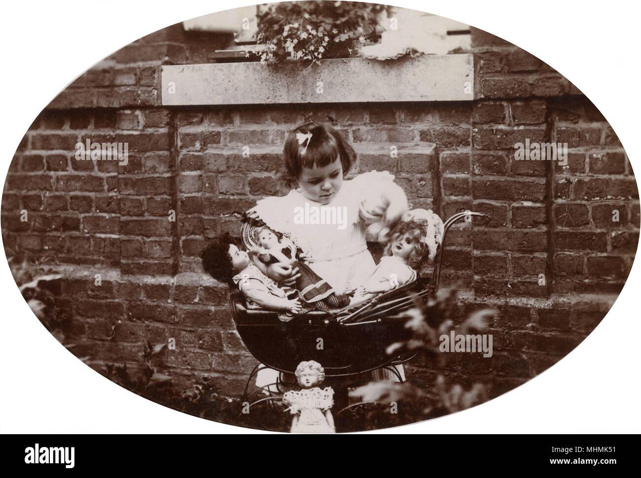 Una niña de Neufchatel, Francia, atiende a dos de sus muñecas en su cochecito mientras se abrocha el otro, mientras que un cuarto es apoyada contra la PRAM. Fecha: circa 1920 ? Foto de stock