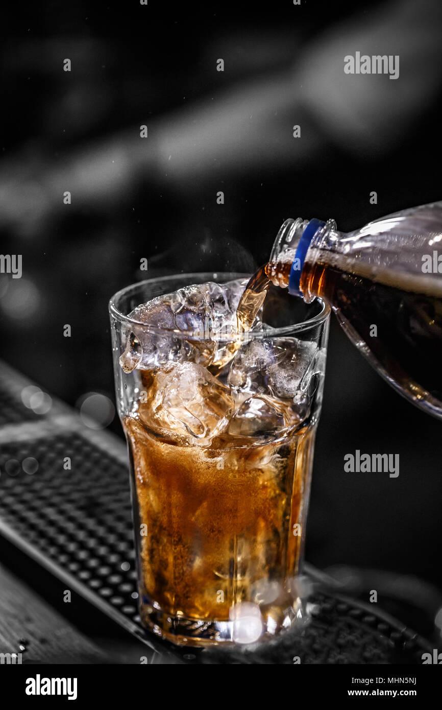 Verter en el vaso de cola llena de cubitos de hielo. Imagen De Stock