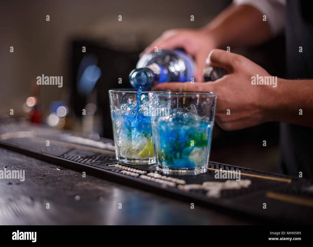 Barman, verter la bebida en un cóctel de vidrio con cubitos de hielo. Imagen De Stock