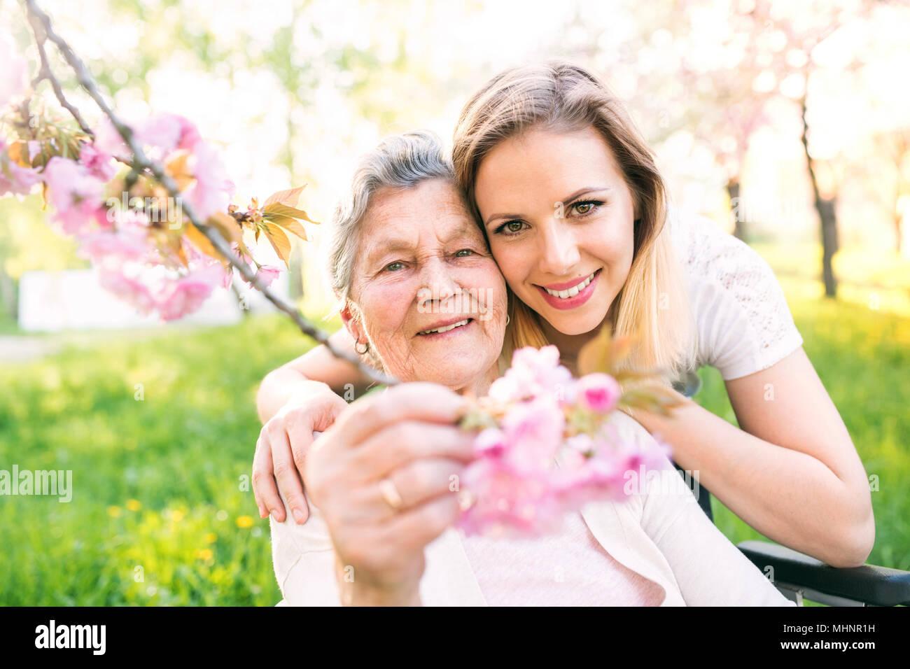 Anciana abuela en silla de ruedas con su nieta en la primavera de la naturaleza. Imagen De Stock