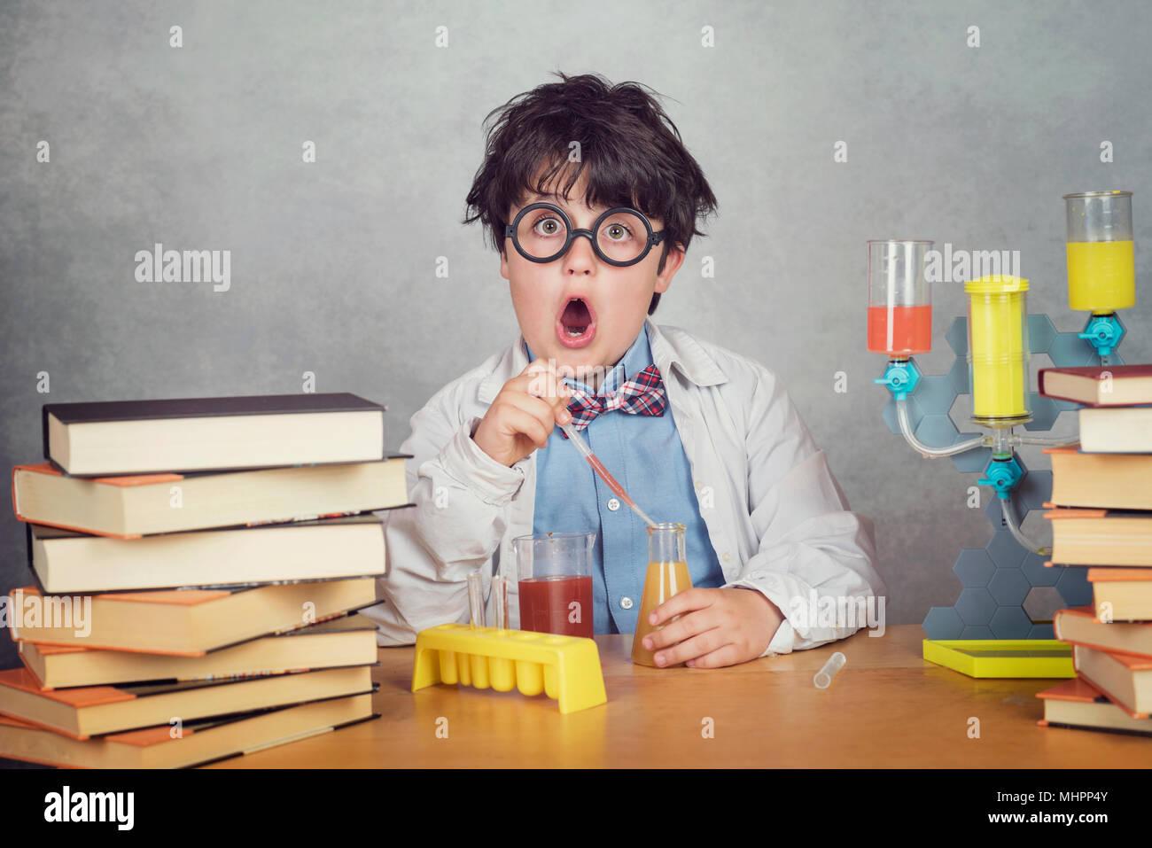 Chico es realizar experimentos científicos en un laboratorio sobre fondo gris Imagen De Stock