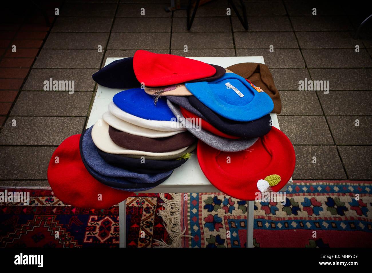Sombreros boina de color diferente en un puesto en el mercado tabla Imagen  De Stock 5fb98258afa