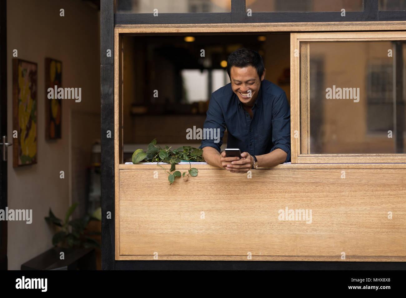 El empresario a través de teléfono móvil en la cafetería Imagen De Stock