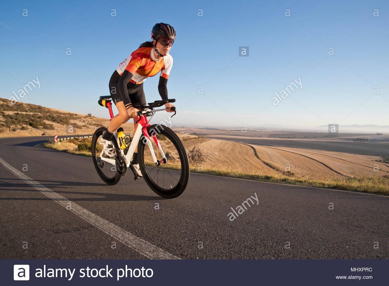 Montando bicicleta carrera ciclista femenina en la soleada carretera abierta Imagen De Stock