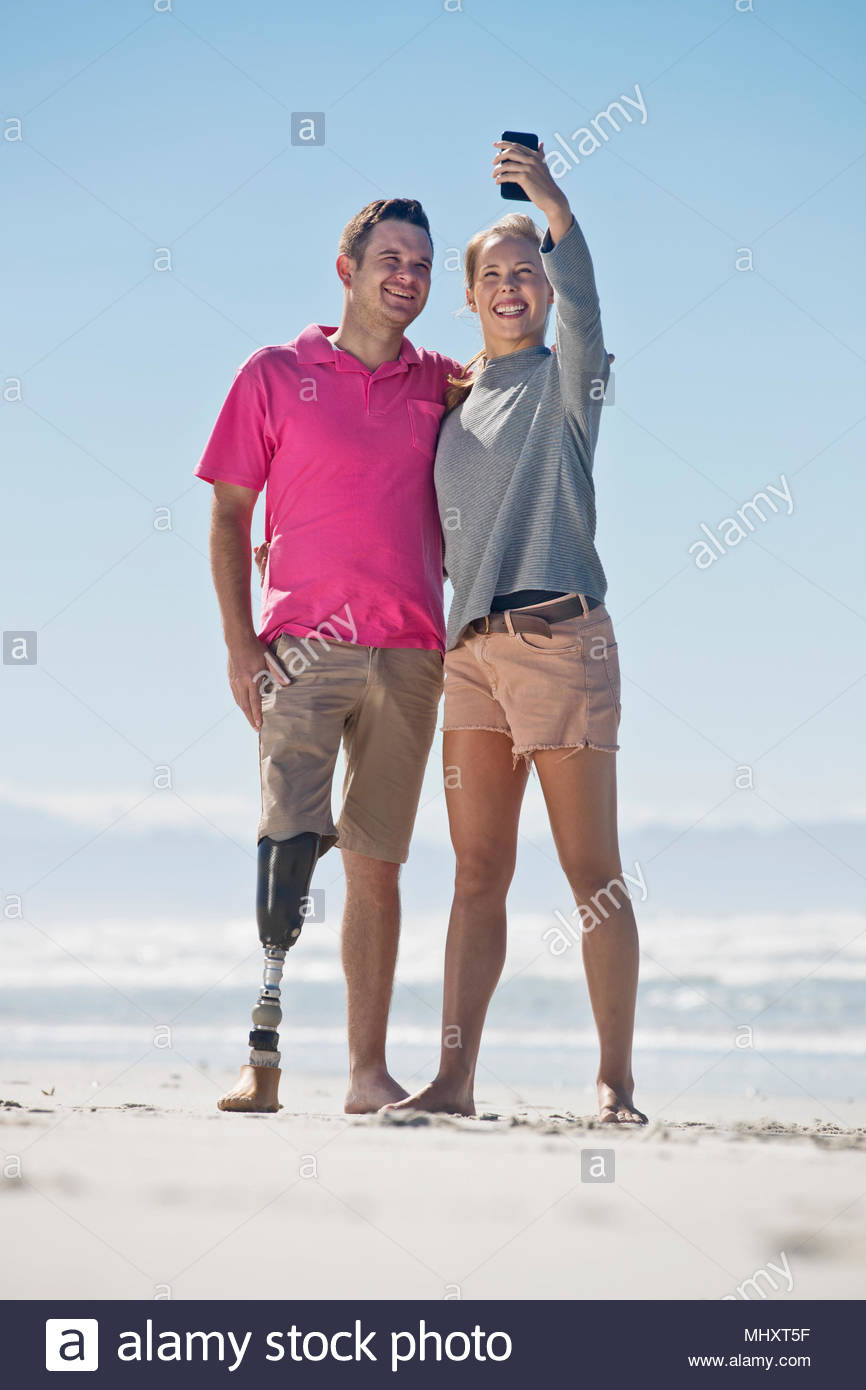 El hombre con la pierna artificial posando para Selfie con pareja femenina mientras que en verano vacaciones de playa en Sudáfrica Foto de stock