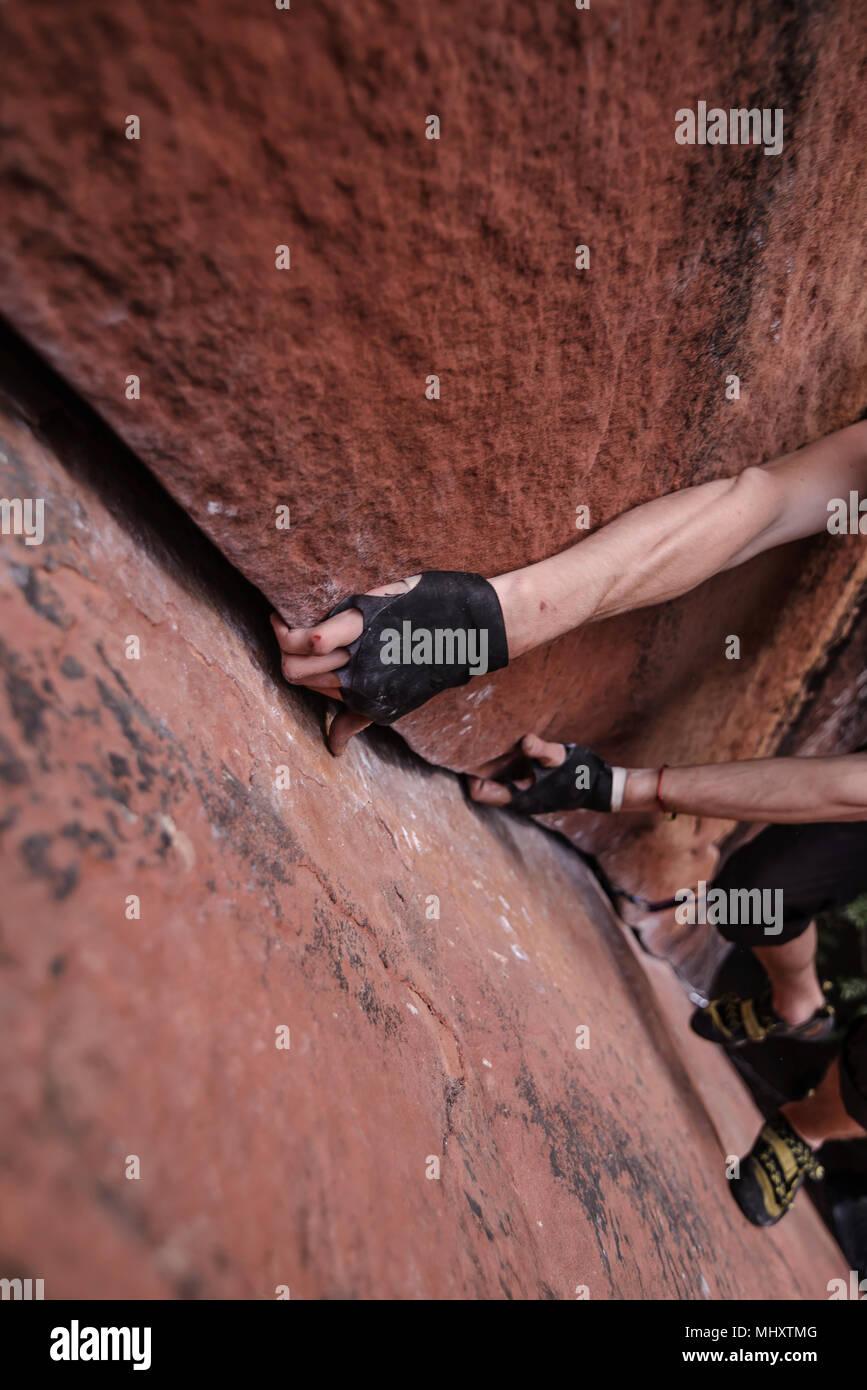 Escalador escalada de roca arenisca, manos agarrando el rock, vista elevada, encalado, provincia de Yunnan, China Imagen De Stock