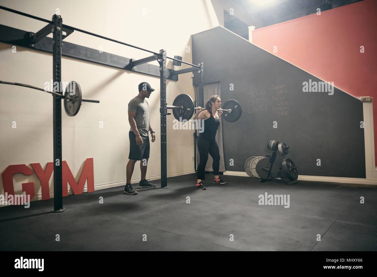 Mujer en el gimnasio con pesas barbell Imagen De Stock
