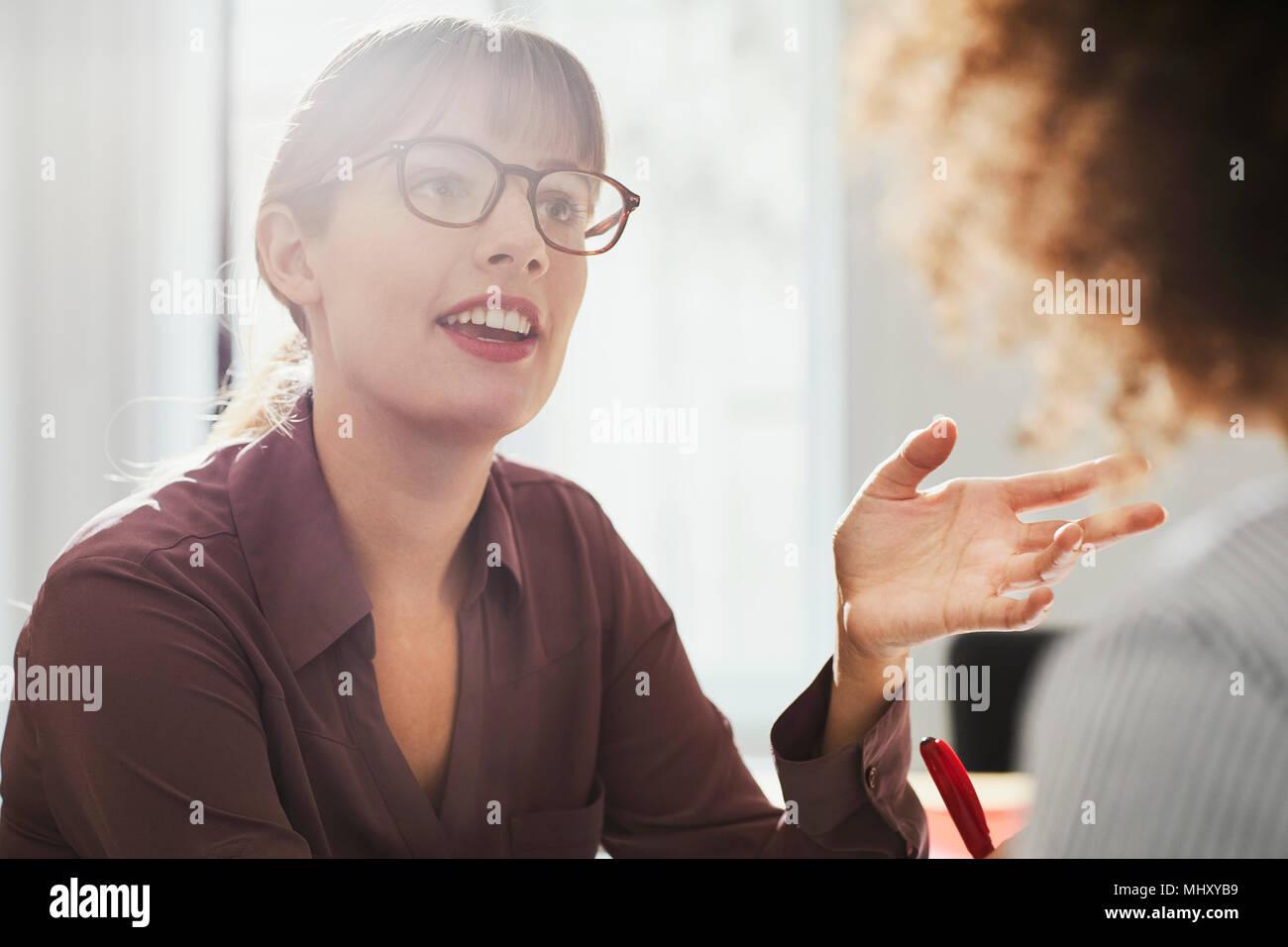 Empresaria en oficina hablando a un colega Imagen De Stock
