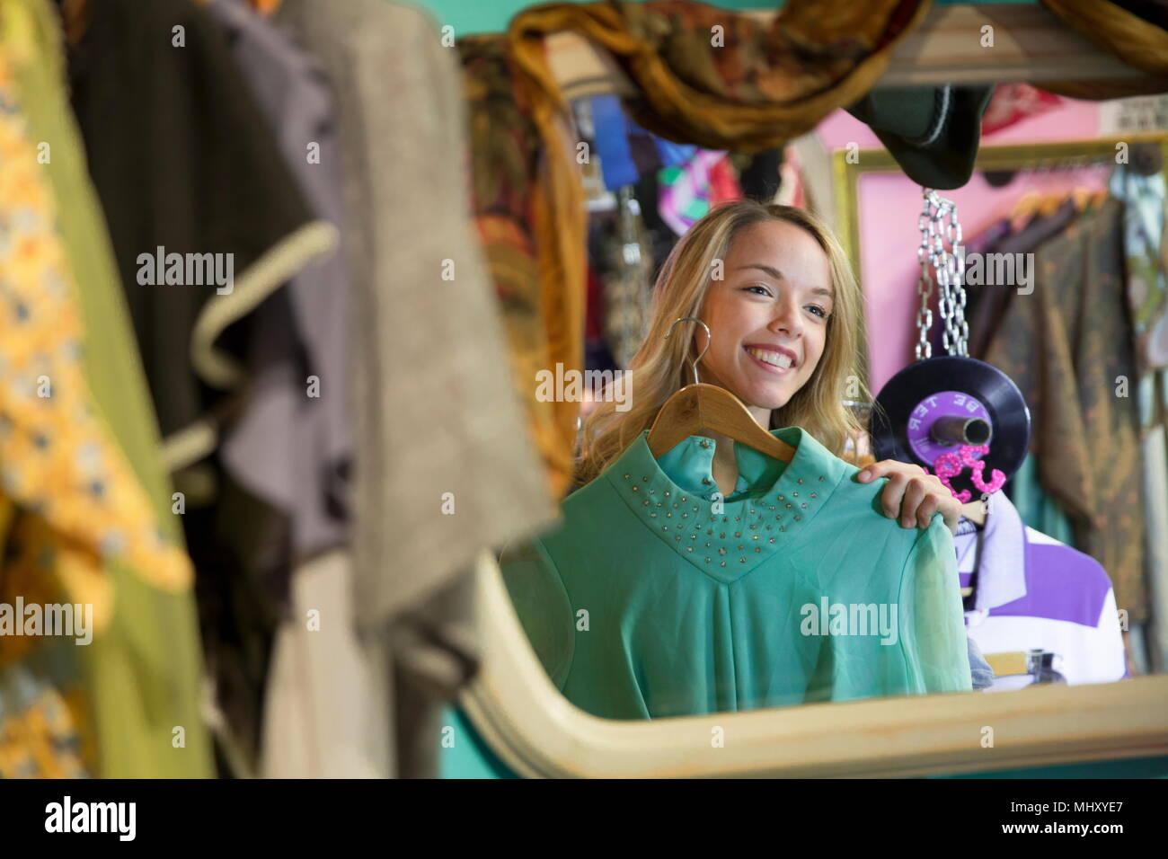 Imagen de espejo de la joven tratando de Vintage ropas en thrift store Imagen De Stock