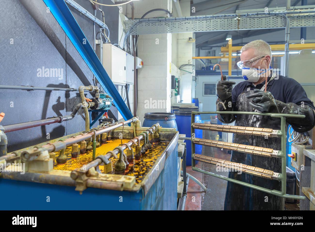 Trabajador colocar componentes en baño cromado en fábrica de galvanoplastia Foto de stock