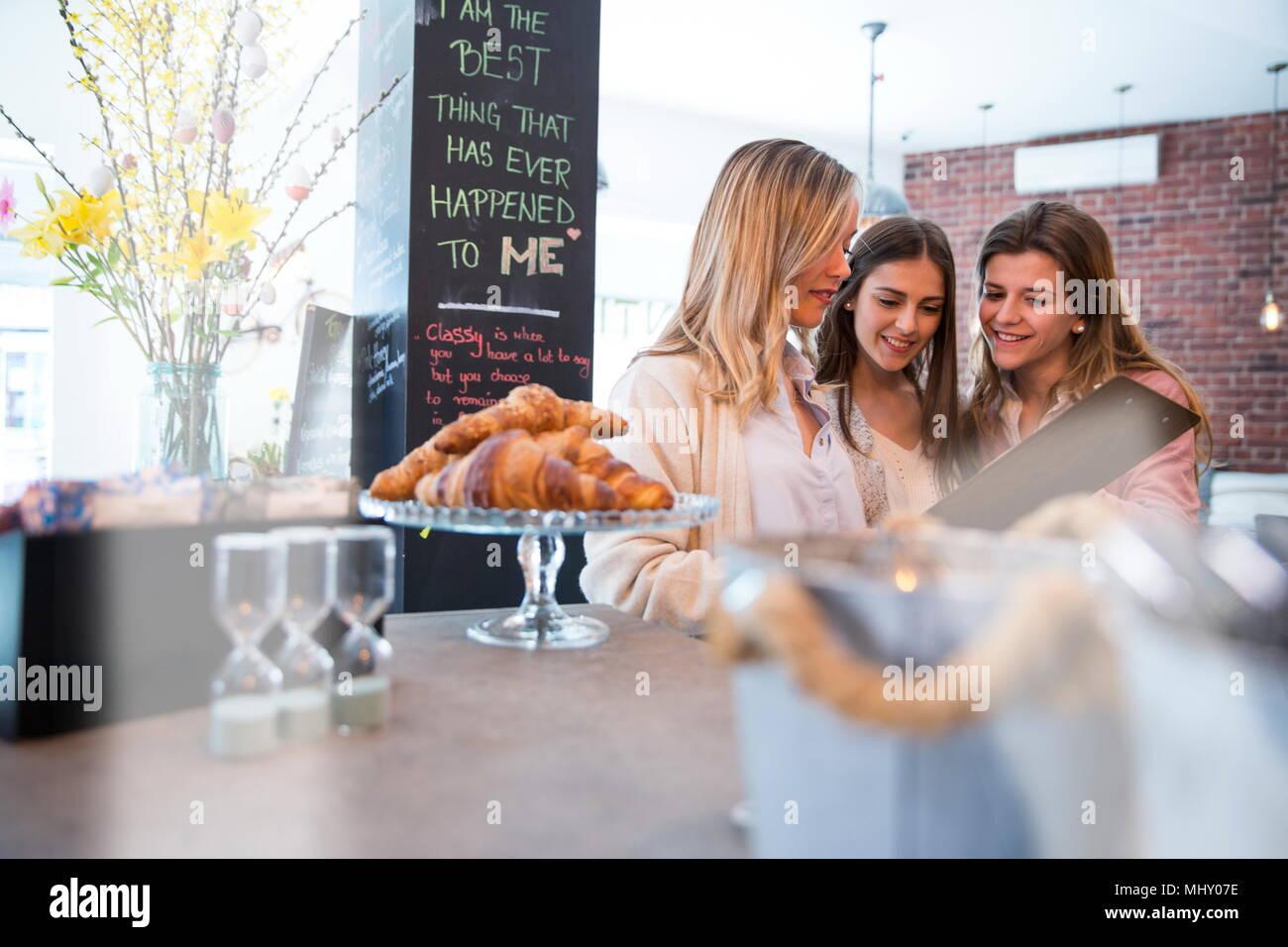 Tres amigas, mirando al menu de cafe Foto de stock