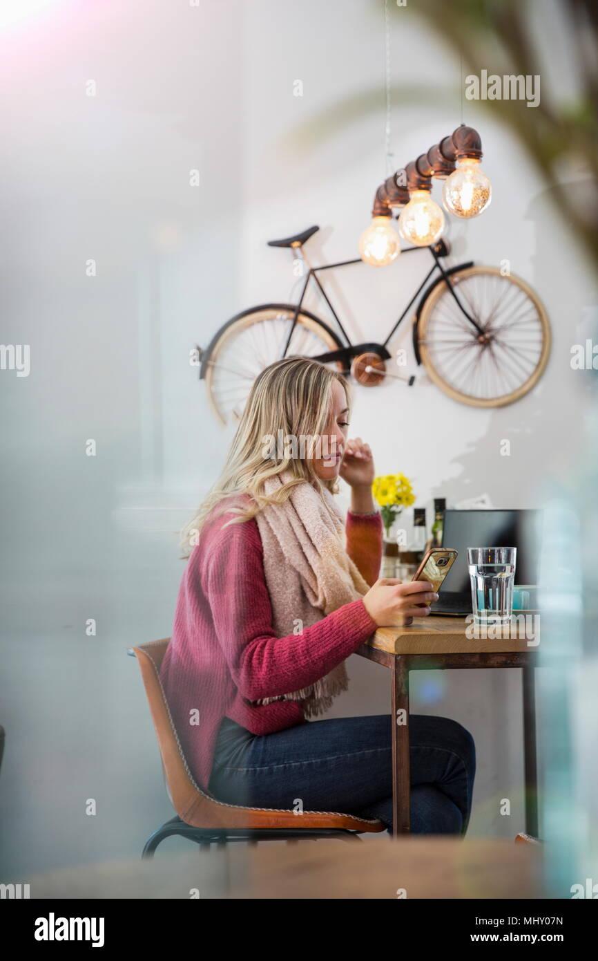 Mujer sentada en la cafetería, mirando el smartphone Imagen De Stock