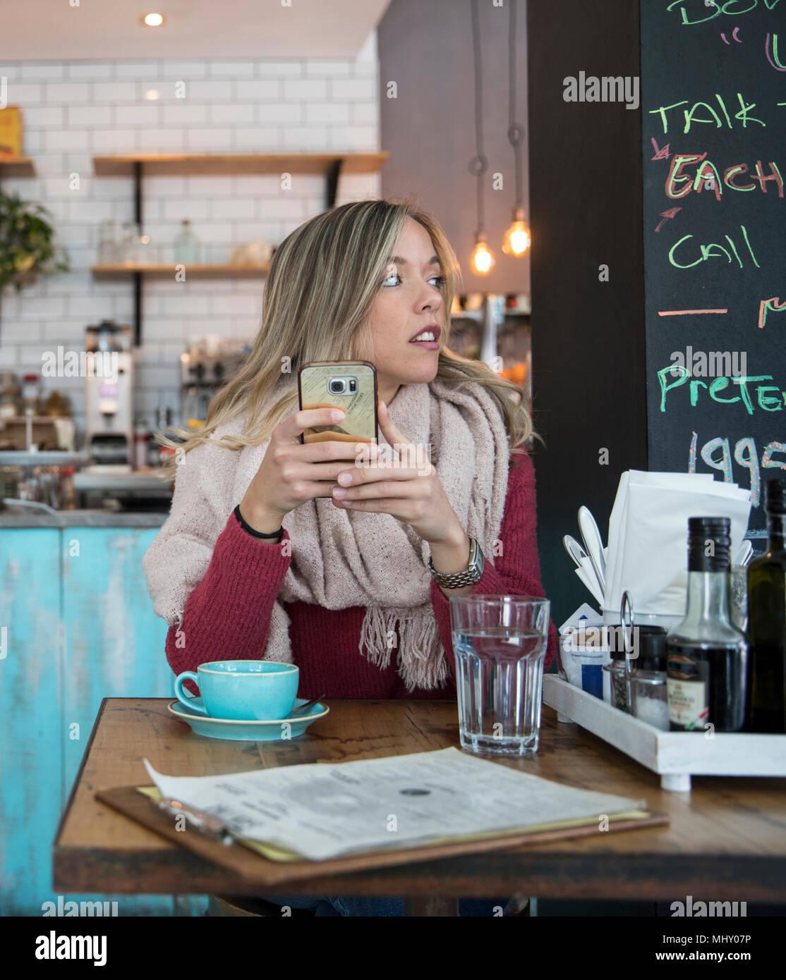 Mujer sentada en el café, sujetando el smartphone, mirando lejos Foto de stock