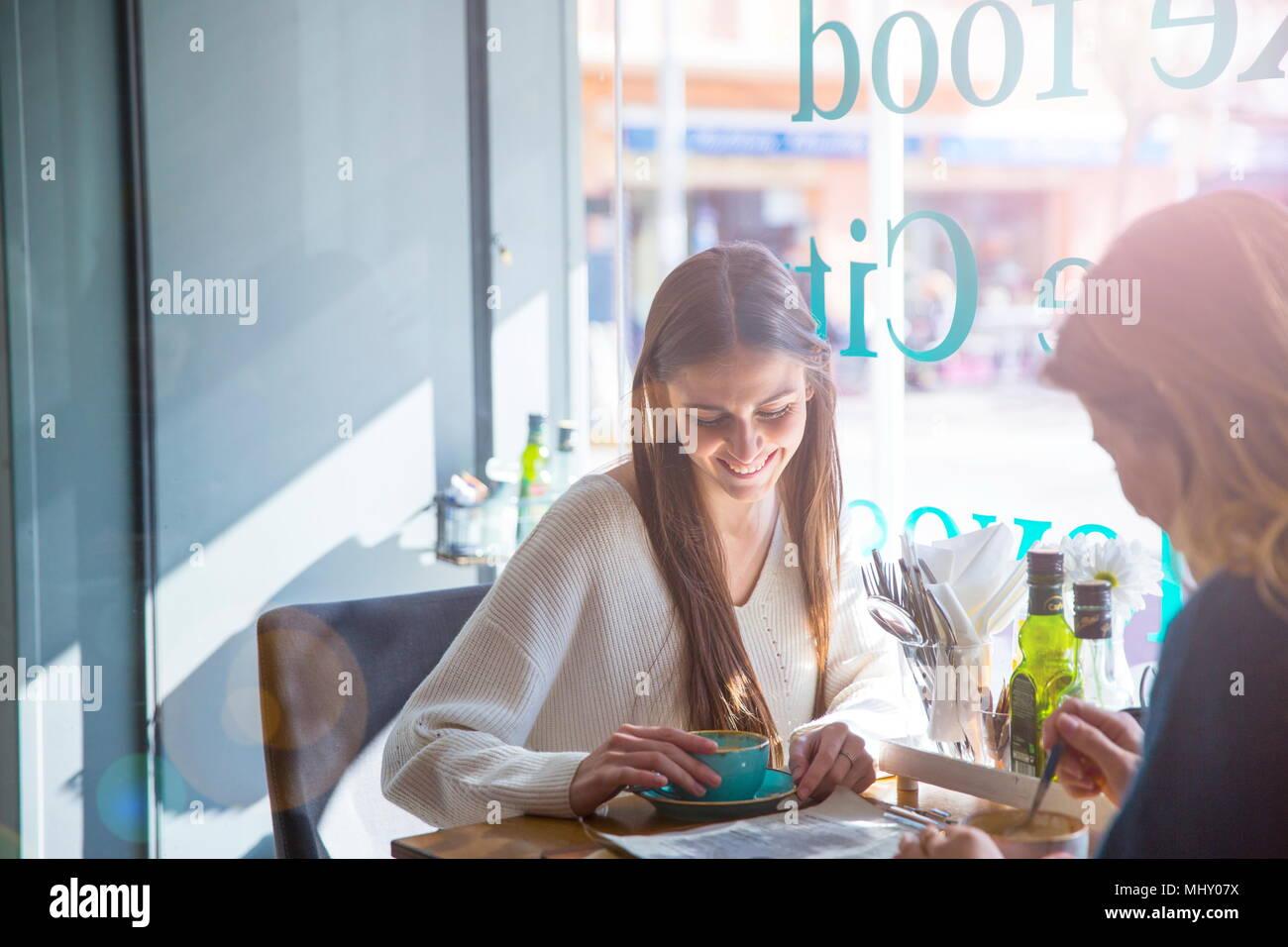 Dos amigas sentados juntos en la cafetería, bebiendo café Imagen De Stock