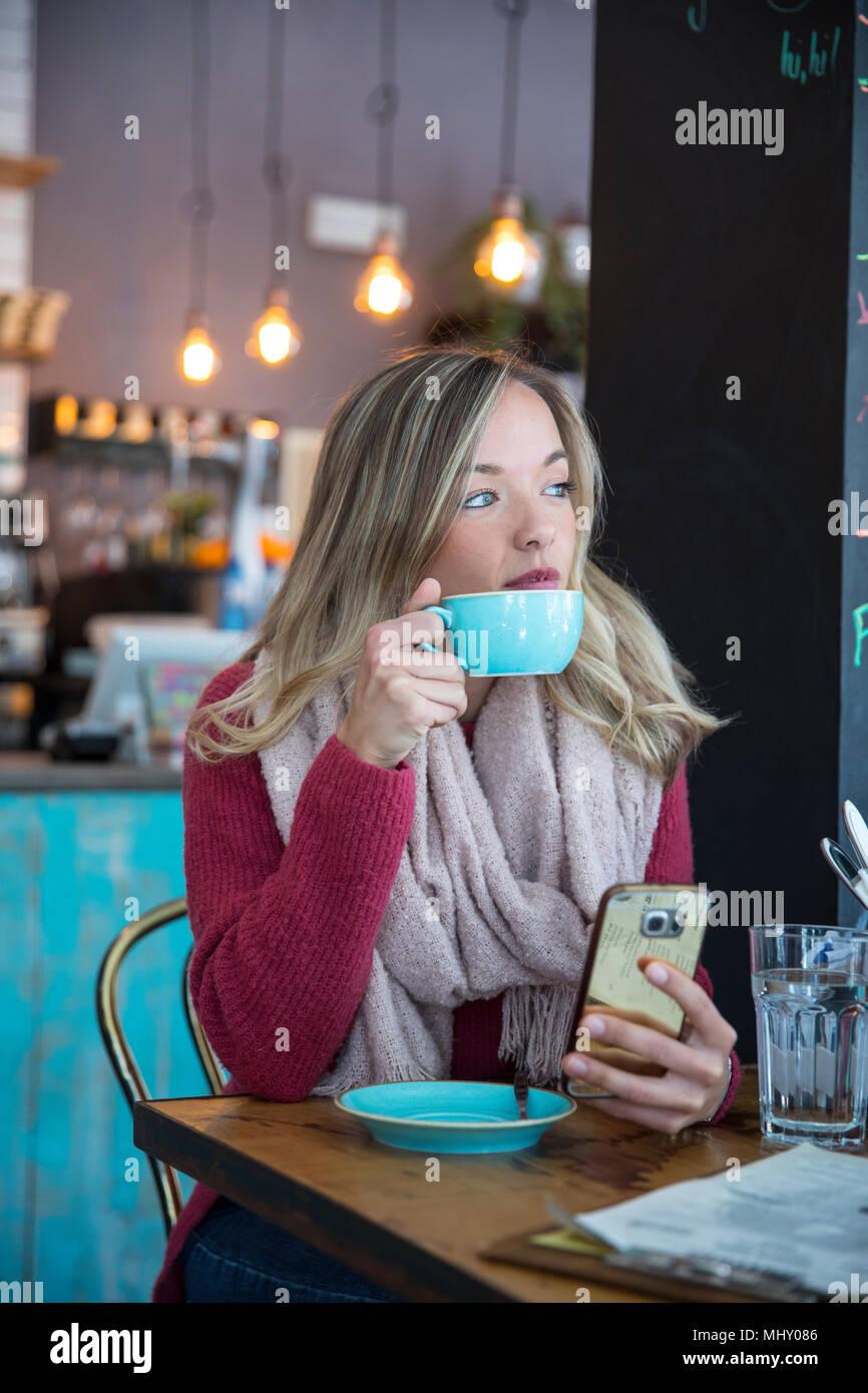 Mujer sentada en el café, sujetando el smartphone, bebiendo café Imagen De Stock