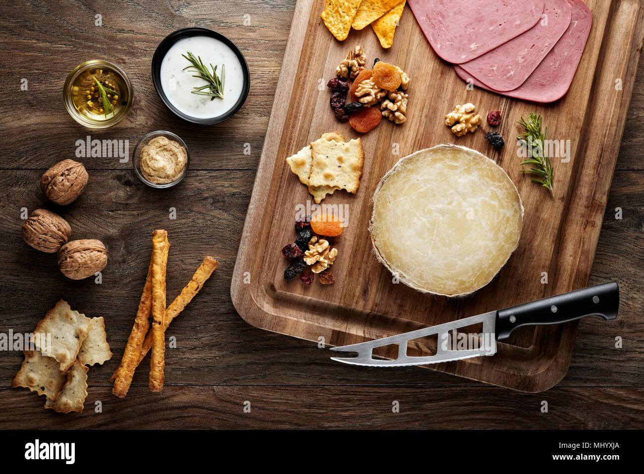 Karaman skinbag turco queso (divle obruk) sobre una mesa de madera decorada con accesorios de madera placa de corte de cuchilla, queso y nueces Imagen De Stock