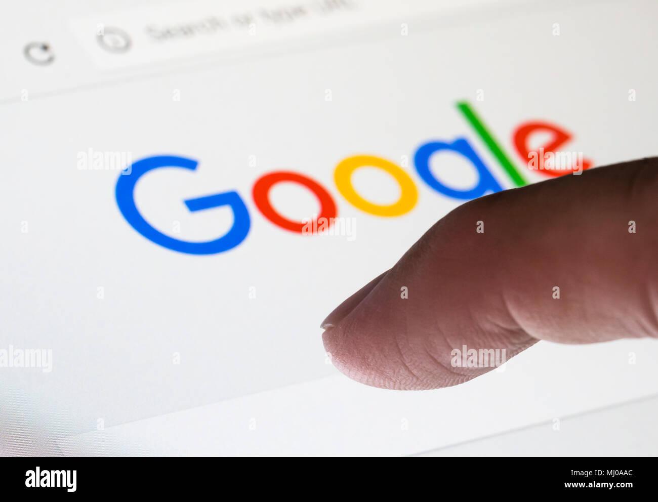 Sobre los dedos para escribir una búsqueda en Google, el motor de búsqueda de Internet Web. Imagen De Stock