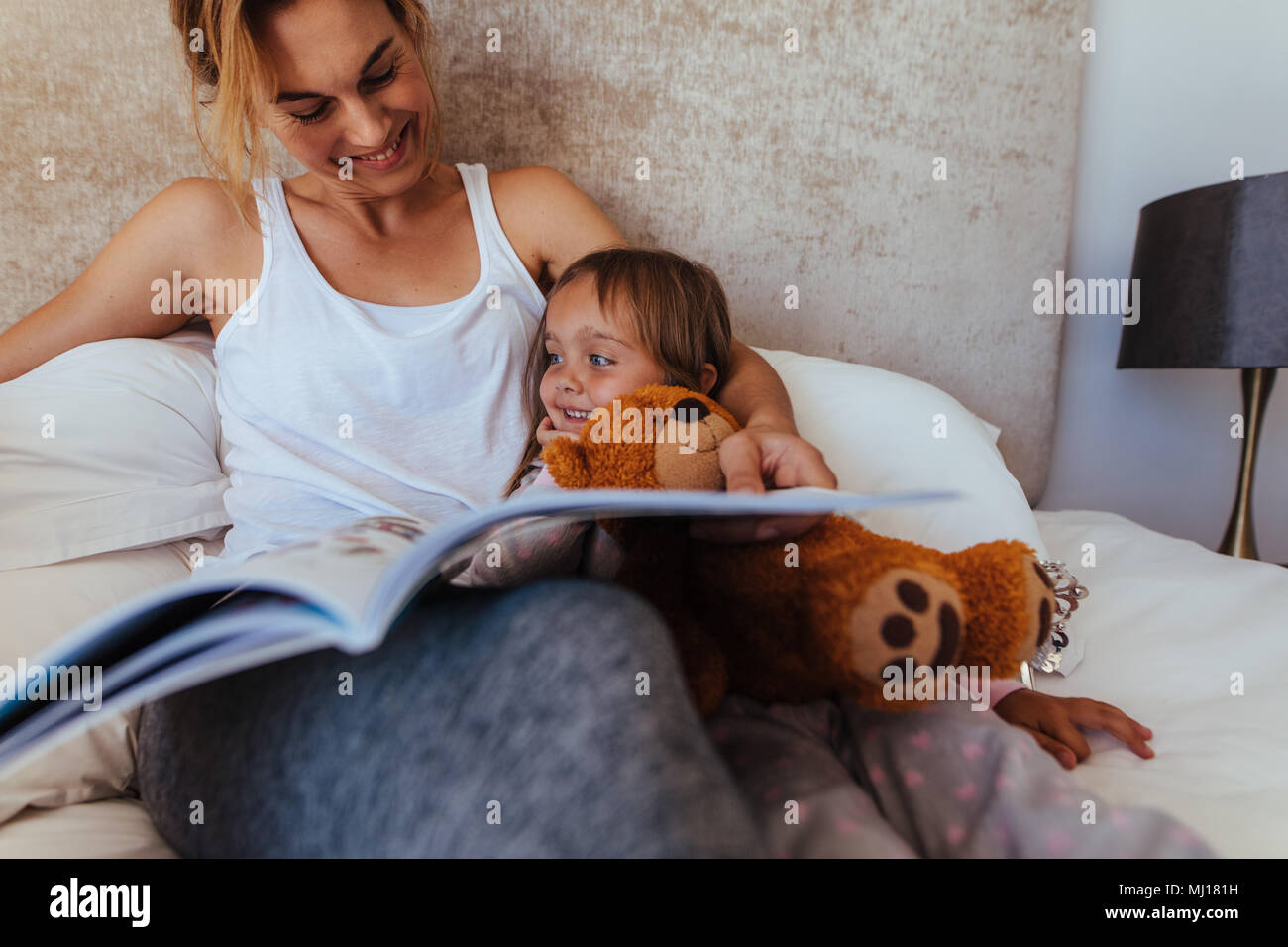 Familia Feliz cuento de lectura en la cama. Mujer mirando su hija y sonriendo mientras lee un libro en el dormitorio. Imagen De Stock