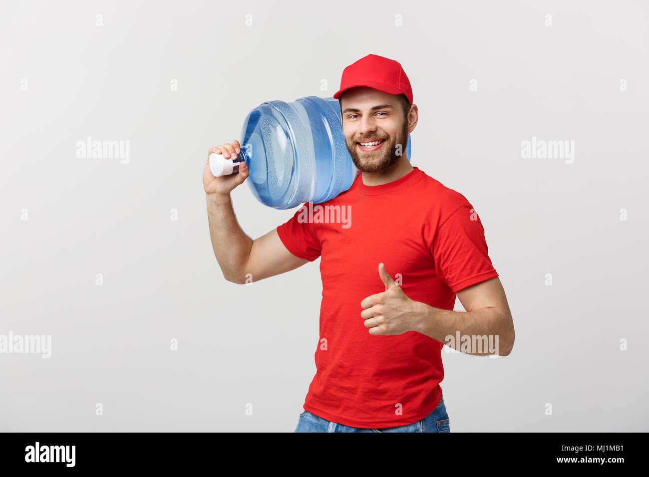 Retrato sonriente courier de entrega de agua embotellada en camiseta roja y tapa de tanque de transporte de bebida fresca y mostrando el pulgar aisladas sobre fondo blanco. Imagen De Stock