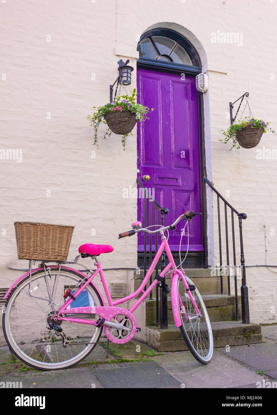 Rosa brillante mujer bicicleta con cesta de mimbre trasero estacionado en  frente de una puerta frontal de madera violeta de una casa de estilo  victoriano ... c67acdd09f4e
