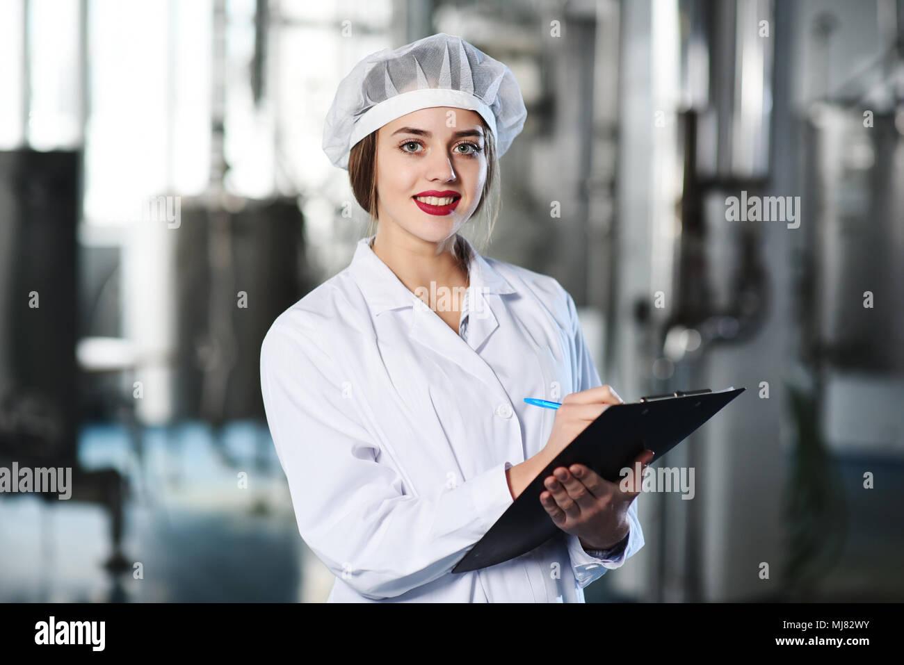 Chica científico o trabajador en blanco uniforme hace que las notas en papel, con el telón de fondo de la moderna fábrica de equipos. Foto de stock