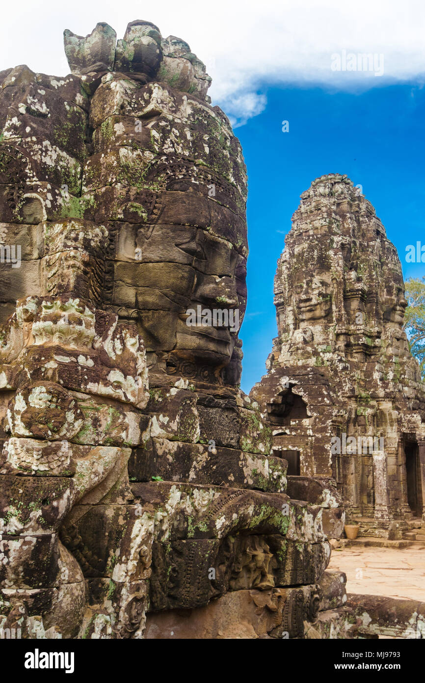 Una cara de piedra monumental del famoso templo Bayon de Angkor, en Camboya. En el fondo, otra torre con dos esculturas de cara puede ser visto. Imagen De Stock
