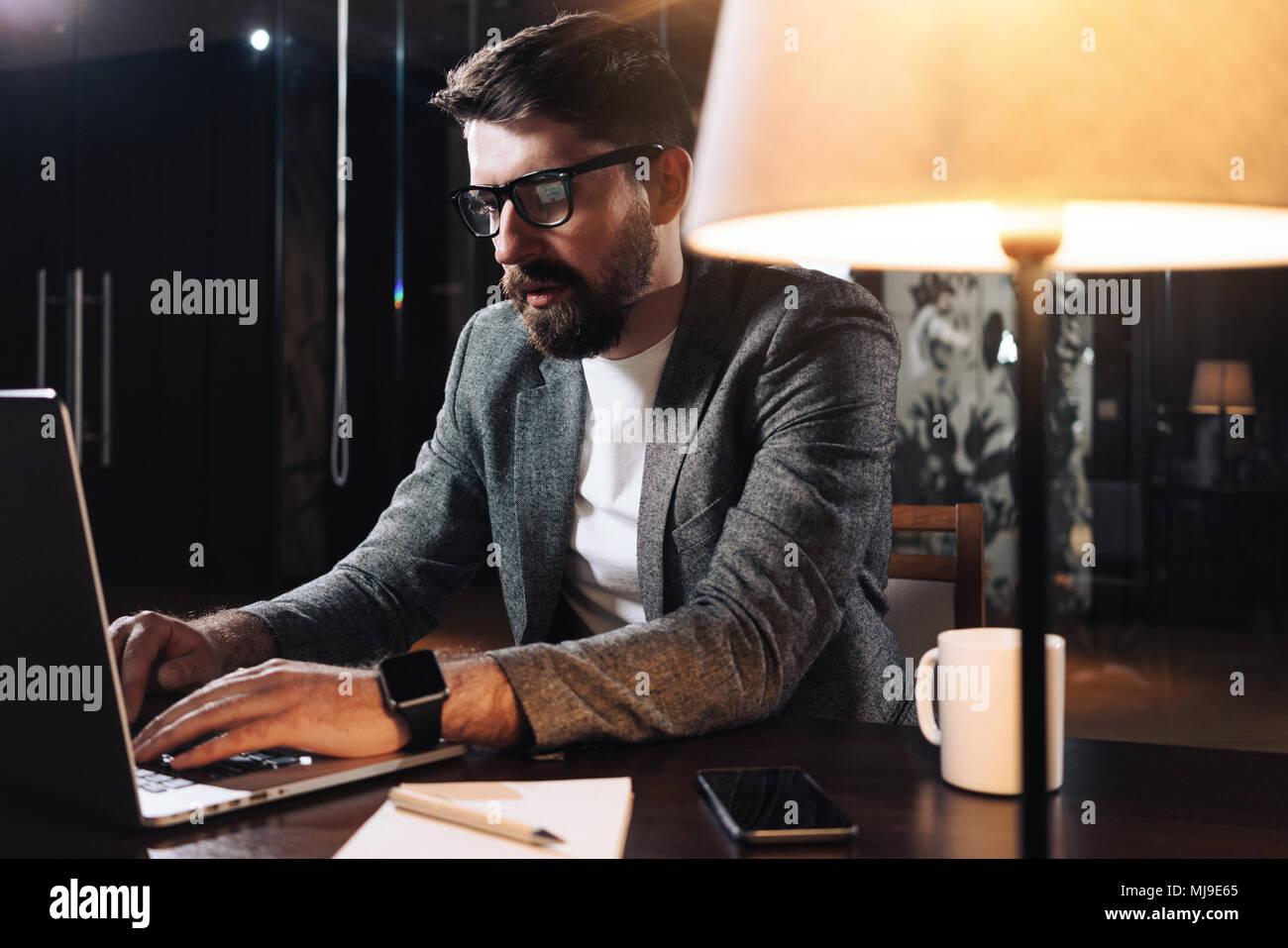 El hombre contemporáneo utilizando equipos portátiles. Empresario barbudo trabajando en la noche en la oficina loft moderno. Gerente de proyecto sentado en formato tablen madera con lámpara Imagen De Stock
