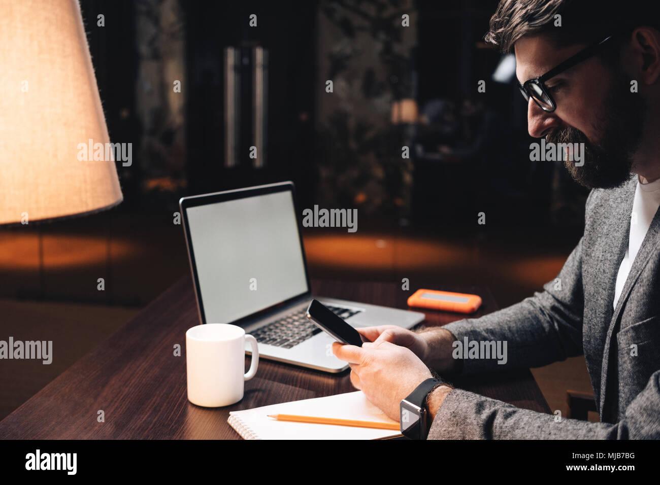 Empresario sonriente con laptop y smartwatch utilizando el smartphone en la noche loft coworking studio. Administrador barbudo está sentada frente al mesa de madera modernos en off Imagen De Stock