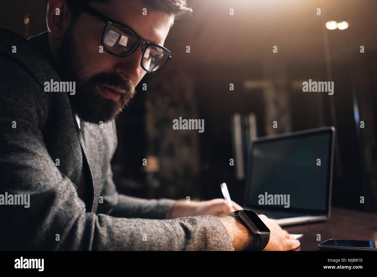 Close-up retrato de hombre barbado portando gafas y smartwatch en la noche coworking espacio loft. Director creativo joven mirando a otro lado. Empresario us Imagen De Stock