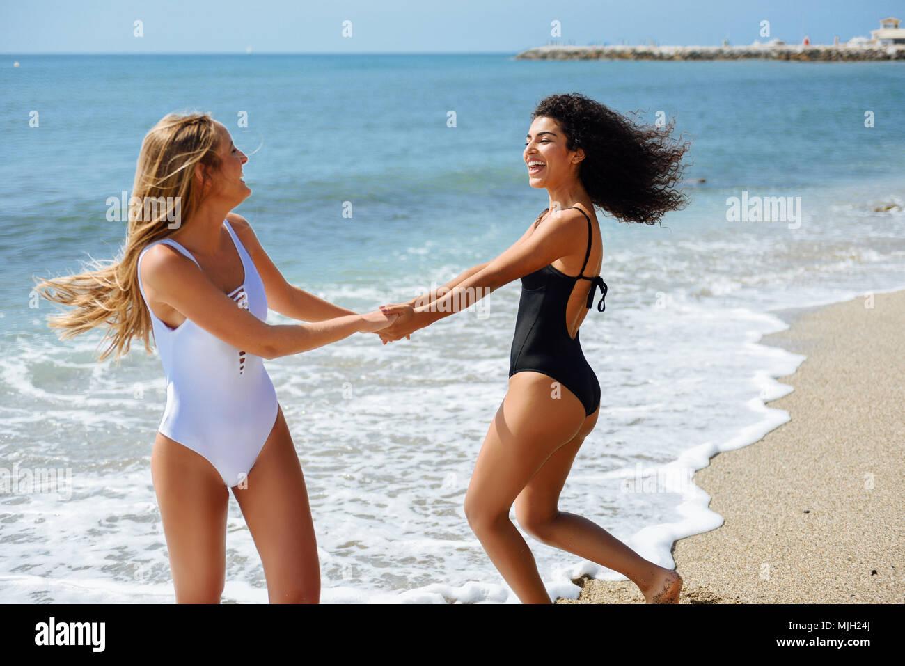 0e3961a28 Dos mujeres jóvenes con bellos cuerpos en traje de baño de divertirse con  sus manos atrapadas