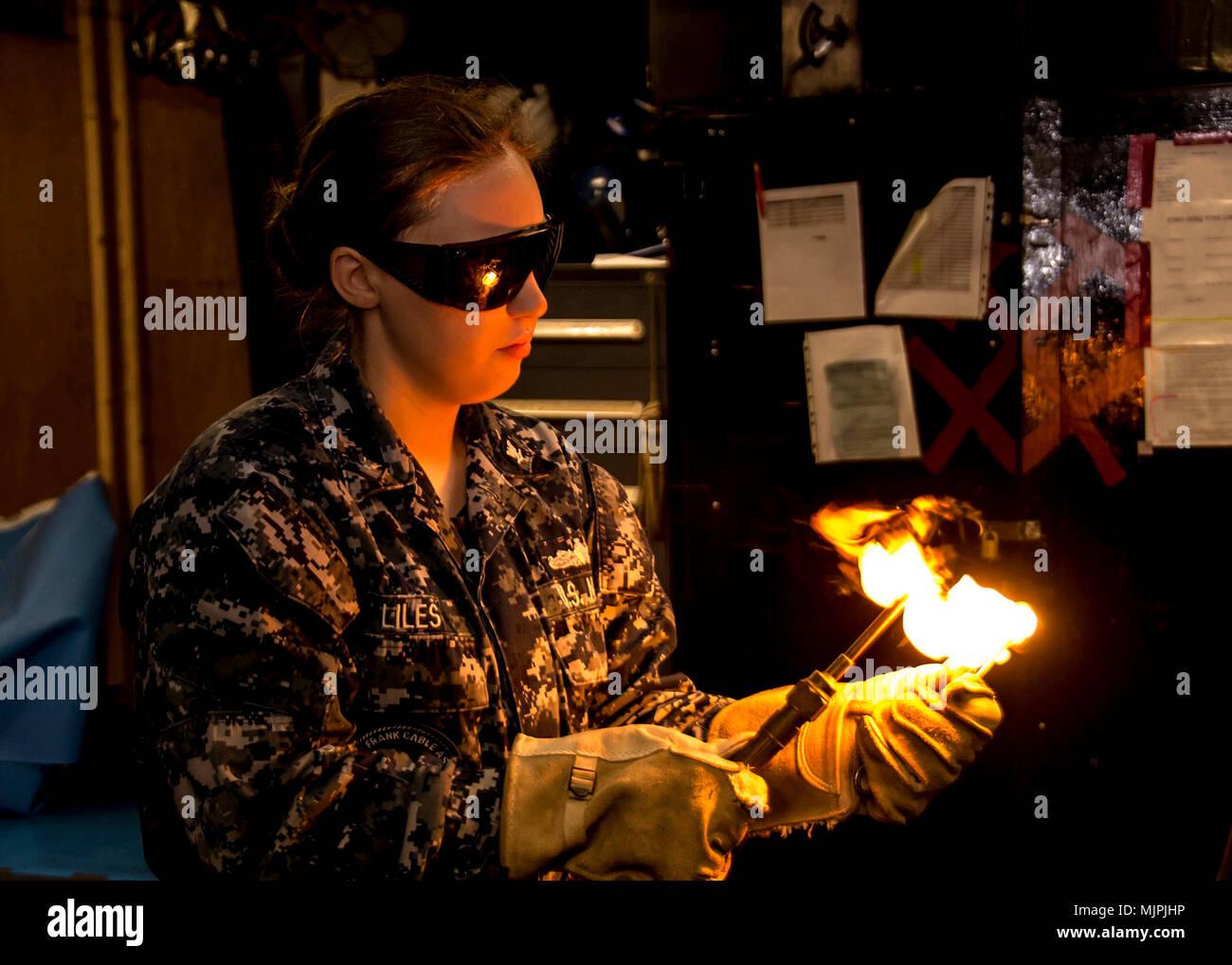 SANTA RITA, Guam (Dec. 8, 2017) Casco Técnico de Mantenimiento de 3ª clase AnnMarie Liles, asignado a la licitación submarino USS Frank Cable (como 40), enciende una antorcha en el tubo tienda a bordo del Submarino USS Emory S. tierras de licitación (39), 8 de diciembre, después de ser nombrado chaqueta azul del año. Liles es deber asignado temporalmente a Emory S. Frank Cable tierra, mientras se encuentra en Portland, Oregon para su dique seco programados de mantenimiento fase de disponibilidad. (Ee.Uu. Navy photo by Mass Communication Specialist 2ª clase Michael Allen McNair/liberado) Foto de stock