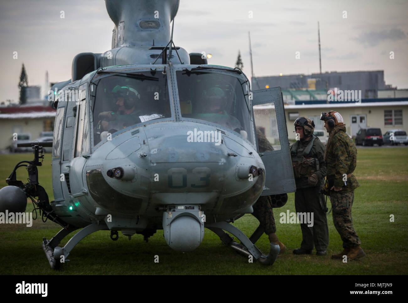 """Un jefe de tripulación de pasajeros placas en un UH-1Y Venom en Camp Foster, Okinawa, Japón, 15 de diciembre de 2017. Luz marina escuadrón de helicópteros de ataque 369 proporciona el Teniente General Brian D. Beaudreault, comandante adjunto de los planes, políticas y operaciones, un vuelo alrededor de la Prefectura de Okinawa para evaluar la calidad de los servicios de la Marine Corps chowhalls. """"Gunfighters"""" dispuestos a actuar en un momento dado es crucial para mantener una más fuerte, más capaz transmita fuerza desplegada en la región del Pacífico Indo-Asia. HMLA-369, Marina, 3er grupo 39 aviones de alas de avión Marino, está actualmente desplegadas bajo Foto de stock"""