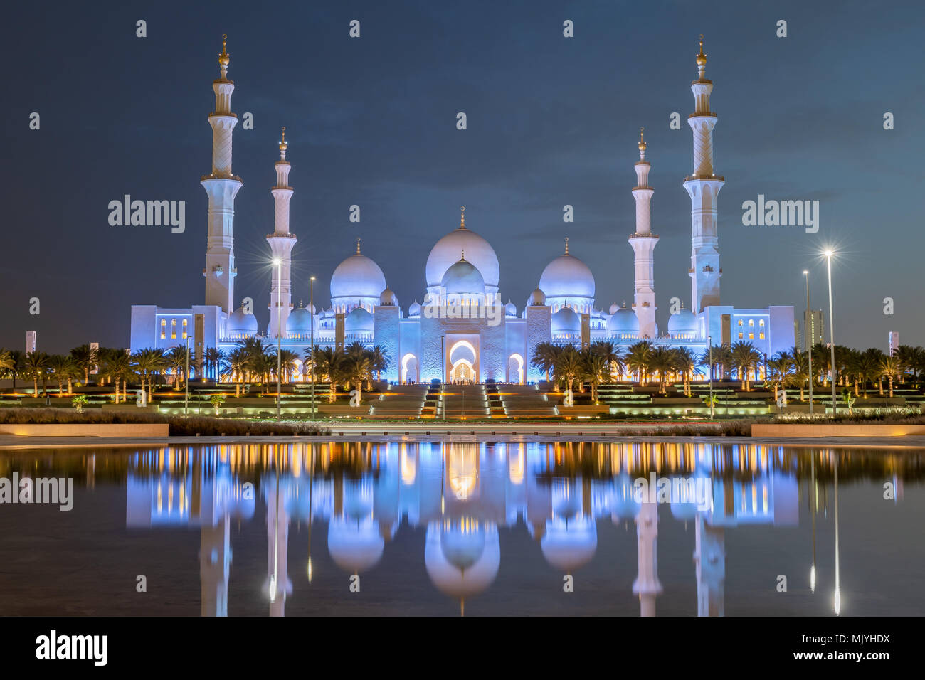 Gran Mezquita de Sheikh Zayed, en Abu Dhabi, capital de los Emiratos Árabes Unidos. Mezquita es construida de mármol blanco italiano. La reflexión en el lago Imagen De Stock