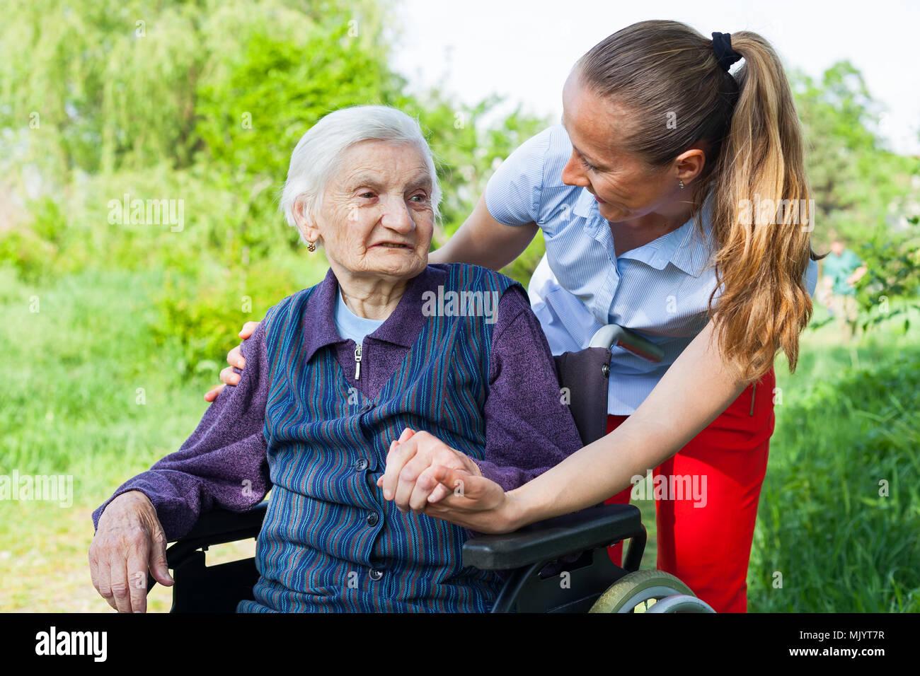 Senior mujer inválida pasar tiempo al aire libre con un amable joven cuidador Imagen De Stock