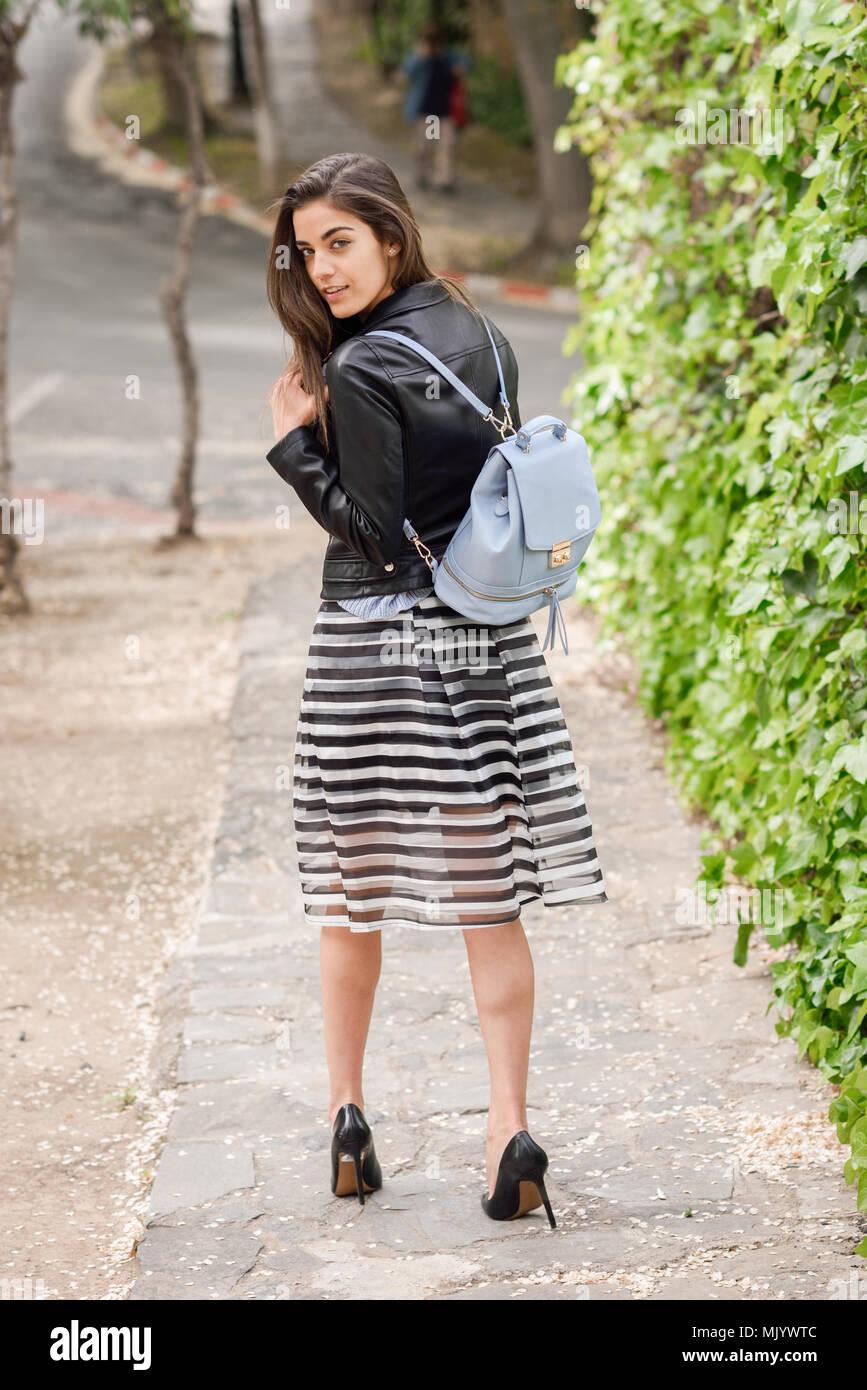 a818b9e0753e3 Volver retrato de mujer joven en el fondo urbano vistiendo ropa casual.  Vestida de falda de rayas y chaqueta de cuero