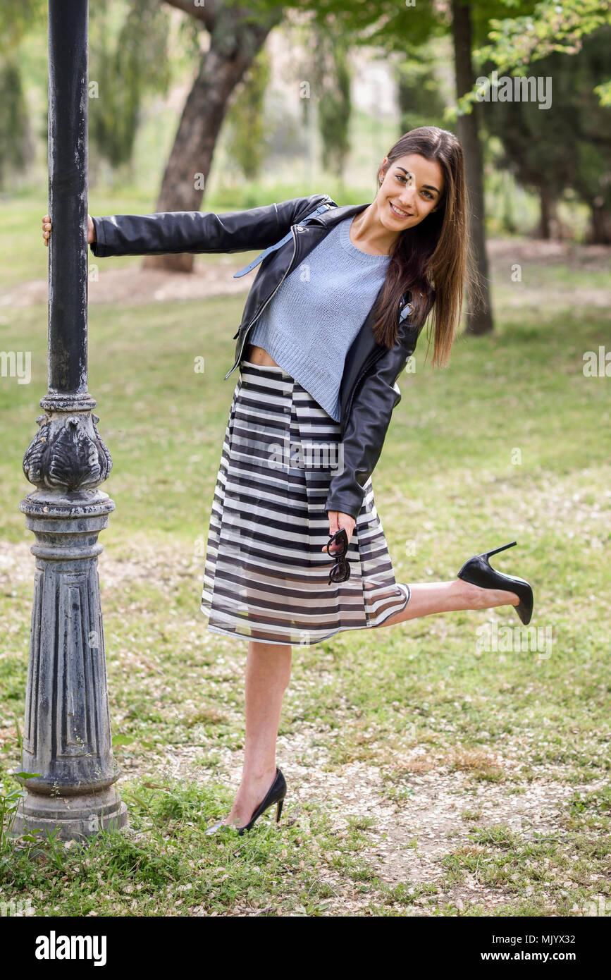 a80538d3269f6 Retrato de mujer joven sonriente en fondo urbano vistiendo ropa casual.  Vestida de falda a