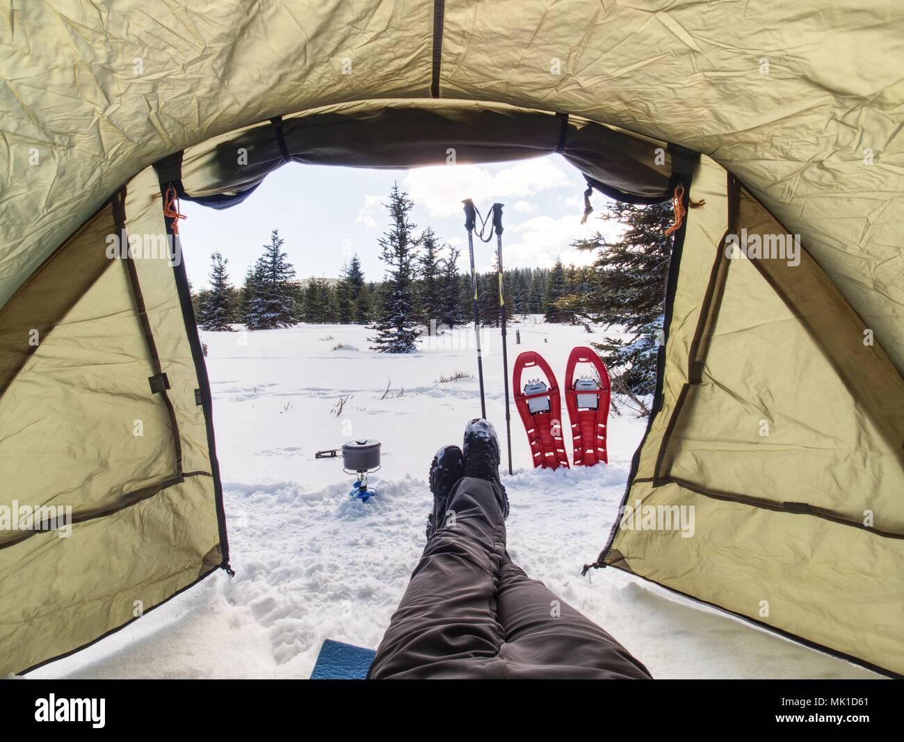 Cocinar en frente de la carpa en la nieve. Caminante camping en montañas en invierno. Hombre cocinar alimentos con cocina de gas portátil y platos ligeros. Una estufa de gas ardiente Imagen De Stock