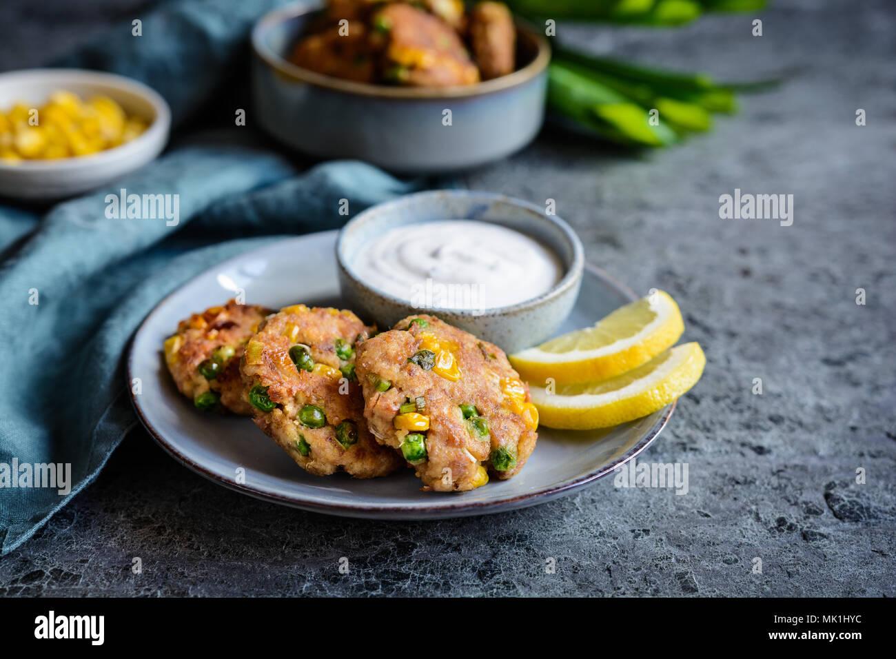 Pasteles de pescado atún saludable con guisantes, maíz y cebollino servidos con crema agria dip Imagen De Stock