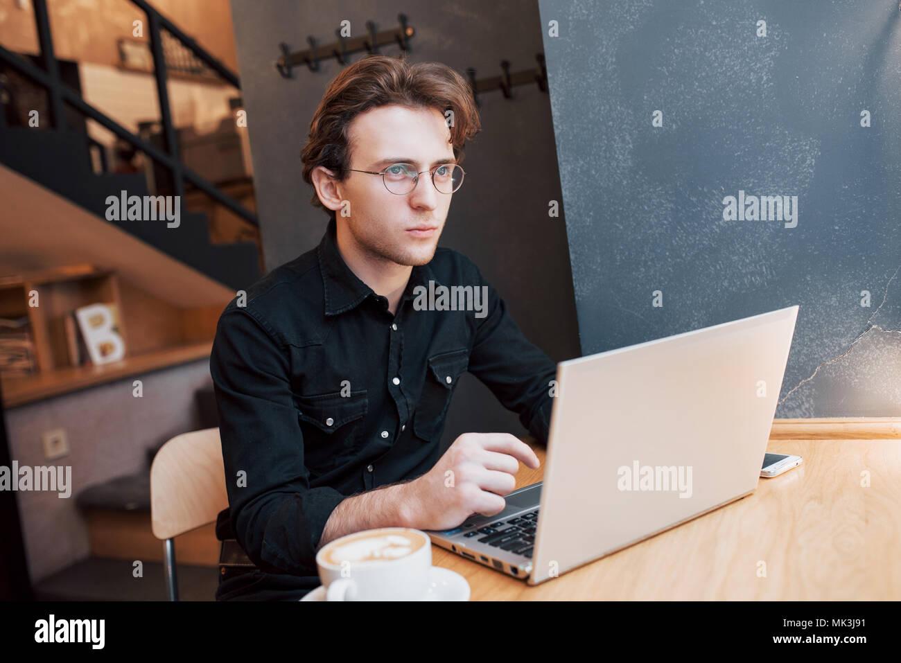Hombre creativo diseñador que trabaja en su computadora portátil mientras esperan órdenes en su café favorito en interiores, estudiante varón trabajando en net-book durante el desayuno por la mañana en la moderna cafetería interior Imagen De Stock