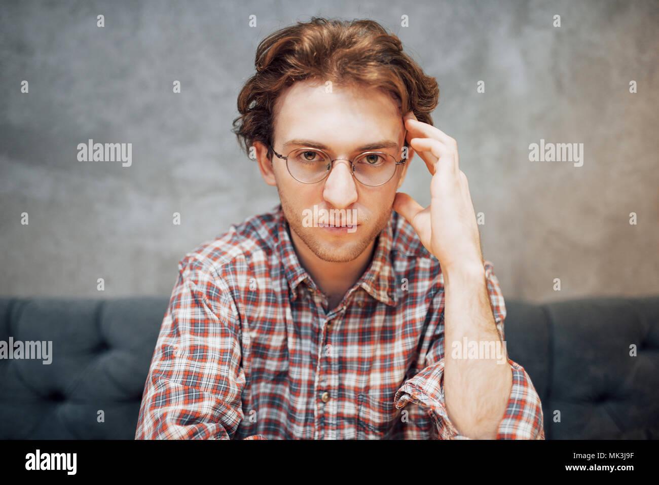 Retrato de guapo y relajado hombre sentado en un café y pensando, trabajo remoto, en busca de la cámara Imagen De Stock