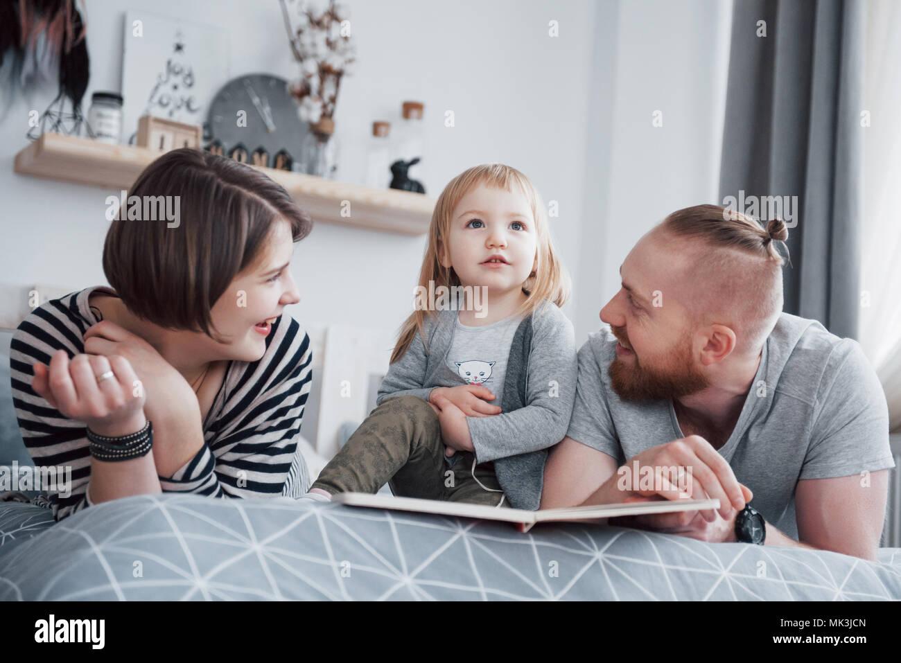 El padre, la madre y la hija leyendo libros infantiles en un sofá en el Salón. Gran familia feliz de leer un interesante libro sobre un día festivo. Los padres aman a sus hijos Imagen De Stock