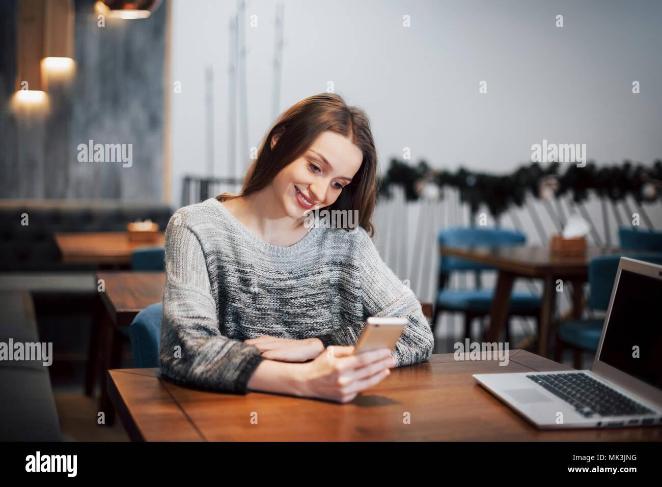 Una atractiva chica de largo cabello negro reflexiona sobre un nuevo proyecto durante una pausa para el café sentado en una mesa en una cafetería Imagen De Stock