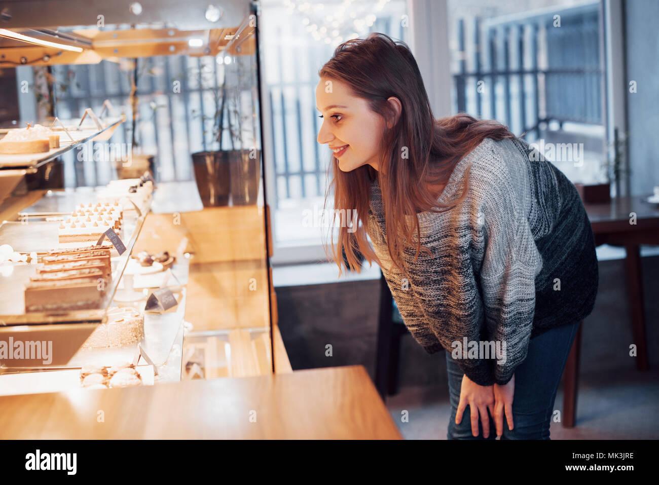 Feliz atractiva chica elegir deliciosos ganaches, praliné y chocolate Imagen De Stock