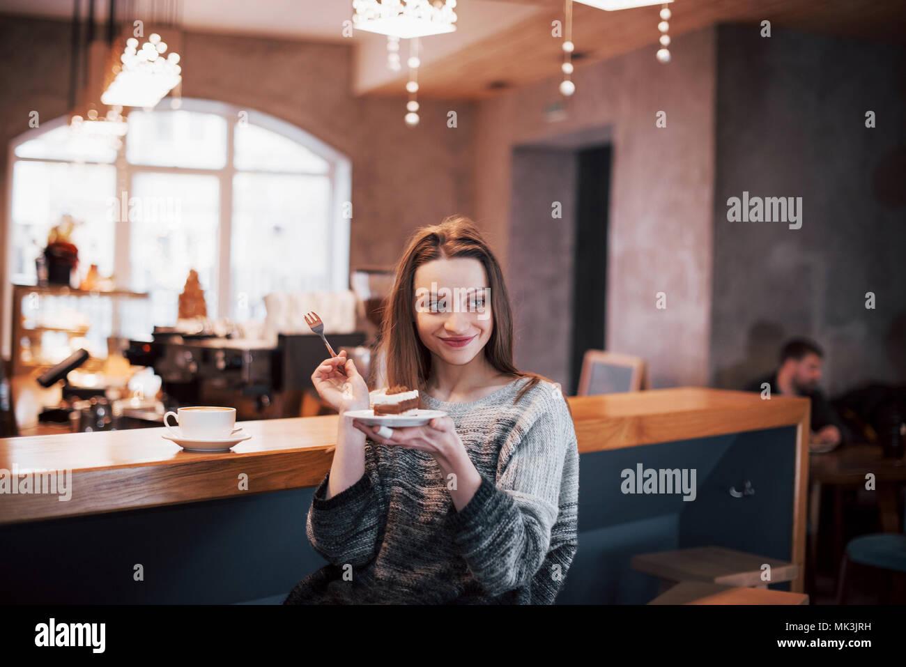 Feliz sonriente joven utilizando el teléfono en un café. Hermosa niña en colores de primavera de moda Imagen De Stock