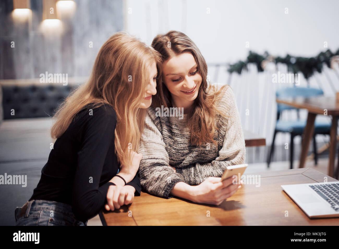 Uno-a-uno de la reunión.Dos jóvenes mujeres de negocios sentado a la mesa en el cafe.niña muestra su amiga la imagen en la pantalla del smartphone. En la tabla se cierra portátil.reunión de amigos Imagen De Stock