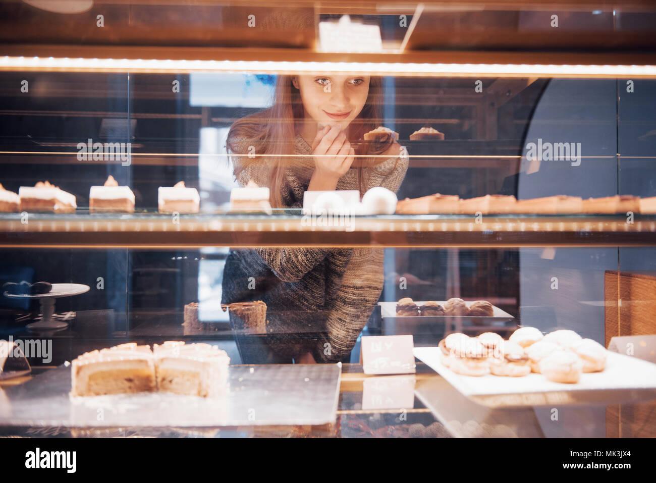 Mujer sonriente a la cámara a través de la vitrina con dulces y pasteles en la moderna cafetería interior Imagen De Stock