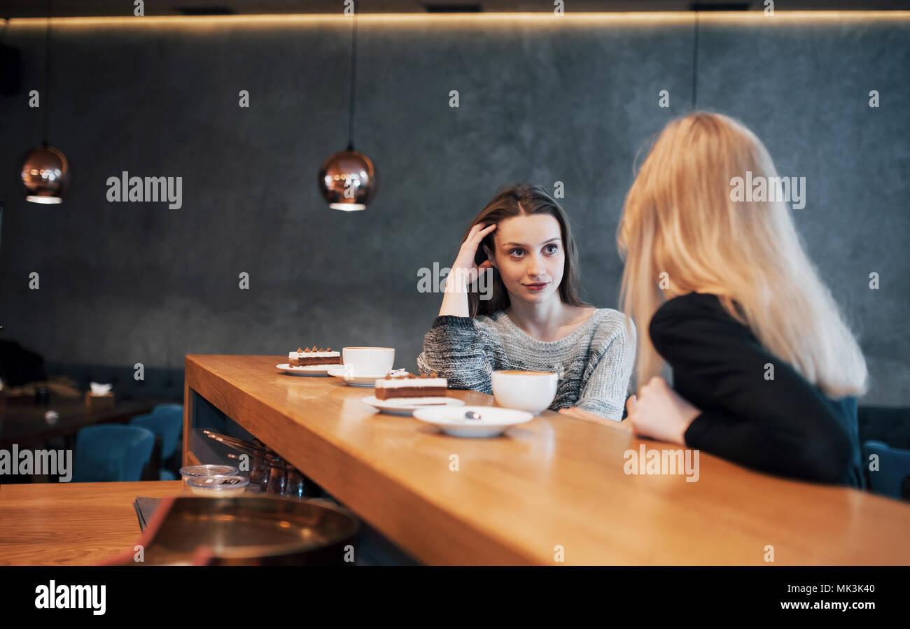 Dos amigos, disfrutando de un café juntos en una cafetería mientras se sientan en una mesa charlando Foto de stock