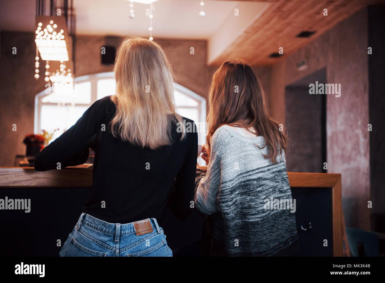 Dos amigos, disfrutando de un café juntos en una cafetería mientras se sientan en una mesa charlando Imagen De Stock